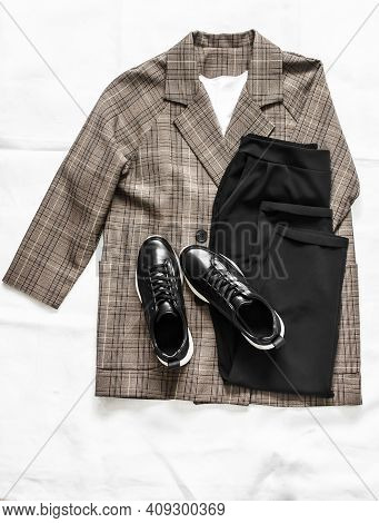 Women's Clothing - Plaid Jacket, Black Trousers And Leather Sneakers Shoes On A Light Background, To