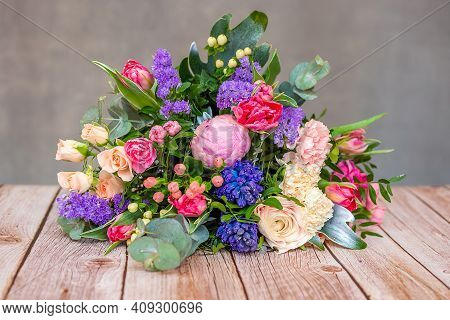 Close Up View Of A Beautiful Bouquet Of Mixed Coloful Flowers On Wooden Table. The Concept Of A Flow