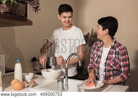 Happy Smiling Mother And Son On Kitchen. Teenage Boy Helping To Cook Food, Mom Washing The Dishes. C