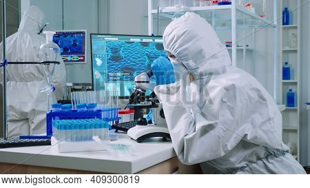 Chemist In Protection Suit Typing On Pc And Analyzing Virus Sample Using Microscope In Scientific La