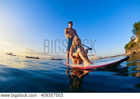 Young Happy Couple Have Fun On Stand Up Paddleboard. Active Paddle Boarder Paddling By Sunset Sea. H