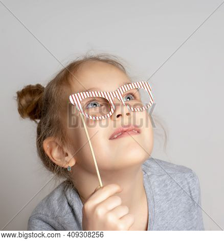 Pensive Little Girl In Carnival Mask With Paper Glasses. Festive Costume For A Masquerade. Attractiv
