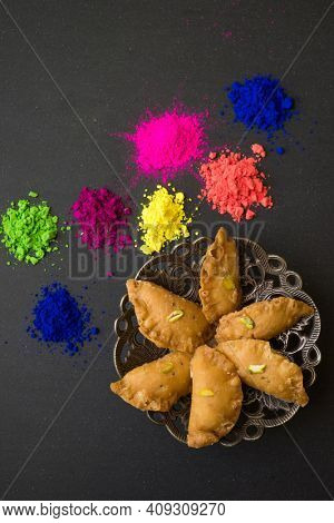 Holi festive special sweet Gujeeya served on a decorative plate, arranged with assorted powder colors. Background image for popular Indian spring festival Holi.