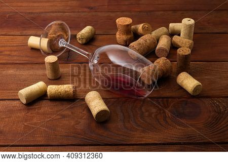 Wine Glass Lying On Its Side With Small Leftover Red Wine Among The Different Used Corks On An Old R