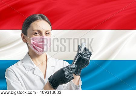 Girl Doctor Prepares Vaccination Against The Background Of The Luxembourg Flag. Vaccination Concept