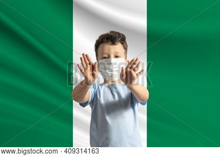 Little White Boy In A Protective Mask On The Background Of The Flag Of Nigeria. Makes A Stop Sign Wi