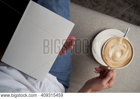 Girl Reading Book And Drinking Coffee, Top View.