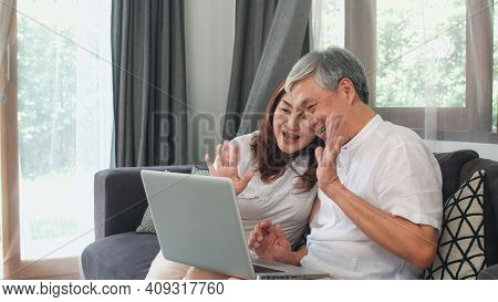 Asian Senior Couple Video Call At Home. Asian Senior Chinese Grandparents, Using Laptop Video Call T