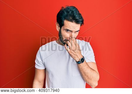Young hispanic man wearing casual white tshirt smelling something stinky and disgusting, intolerable smell, holding breath with fingers on nose. bad smell