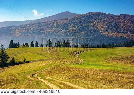 Mountainous Countryside In Autumn. Rural Road Through Grassy Pastures On Hills Rolling In To The Dis