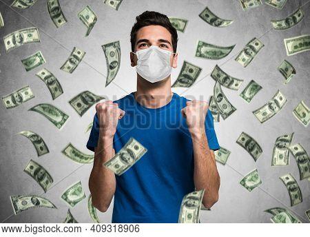 Young masked man enjoying a rain of money during covid coronavirus pandemic