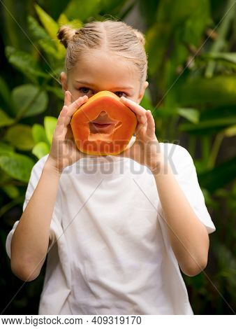 Charming Little Girl With Fresh Papaya. Caucasian Girl Holding Slice Of Papaya Fruit In Front Of Her