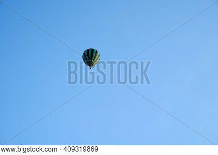 Black And Green Hot Air Balloon High In A Blue Sky. Watermelon Hot Air Balloon. Active Recreation On