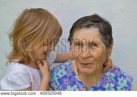 Great-grandmother And Great-grandchild Spending Time Together Happily. Smiling Senior Woman And Shy