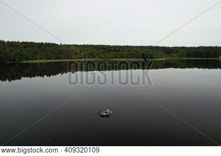 Top View Of A Lone Fisherman On A Boat In The Early Morning Fishing On The Lake