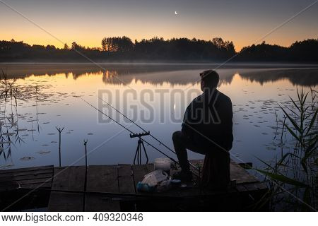 At Night, A Fisherman Sits On The Pier With Fishing Rods For Fishing On The Lake