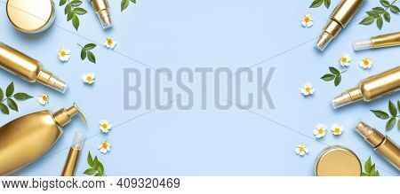 Cosmetic Mock Up Gold Bottles. Cosmetics, Spring White Flowers Green Leaves On Blue Background. Cosm