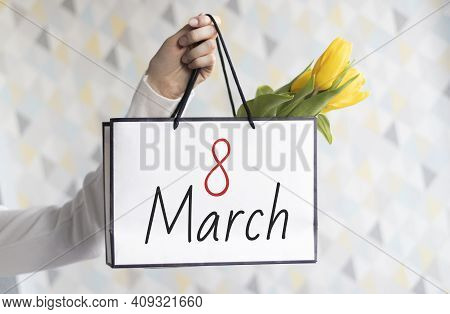 Package With Flowers In Hand For Women's Day On March 8 With The Number And Month. Beautiful Light B