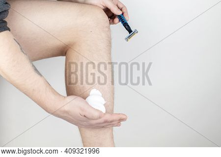 A Man On A White Background Shaves His Legs. Hairy Legs And Care For Them. Gender Equality Concept.