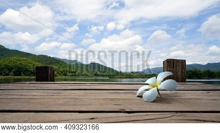 Perspective View Of White Floral Drop On Wooden Bridge Lake With Green Mountain, Bright Blue Sky And