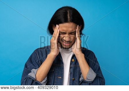 Asian Young Man Is Suffering From Headaches And Stress Due To Migraine. The Young Man Squeezed His H