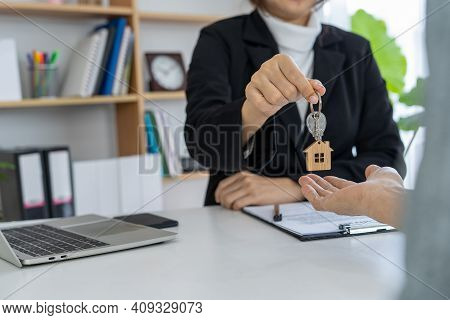 Real Estate Agents Give Key To Homeowner  After Agreement To Buy-sell.