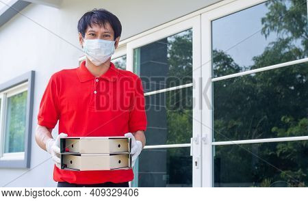 Delivery Man In Red Uniforms, Wearing Masks And Gloves, Carries A Pizza Box, Home Delivery Service F