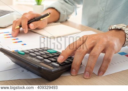 Businessman Using A Calculator To Calculate The Numbers From Business Financial Report On His Desk I