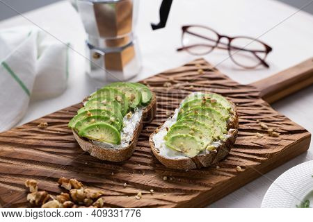 Sliced Avocado On Toast Bread With Nuts. Breakfast And Healthy Food Concept.