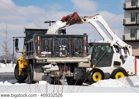 A Large Metal Bucket Of A Tracked Excavator Loads Snow From A City Road Onto A Truck Body Remove