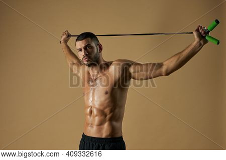 Focused Strong Sportsman Holding Skip Rope Above The Himself In The Studio