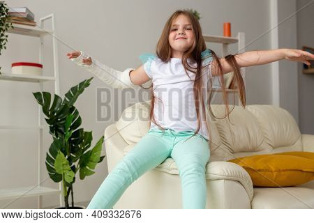 Child With A Cast On A Broken Wrist Or Arm Smiling And Having Fun On A Couch. Positive Attitude, Rec