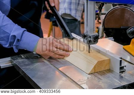 Professional Man Carpenter Hands Using Electric Bandsaw Tool, Cutting Piece Of Wood At Workshop - Cl