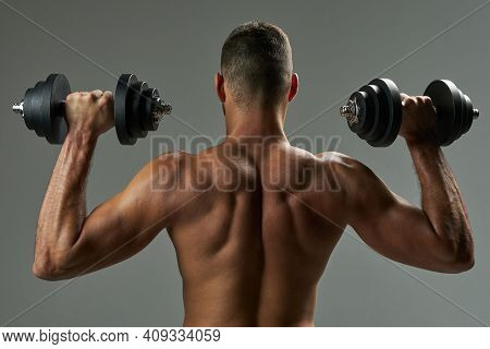 Adorable Strong Bodybuilder Doing Building Up Muscles With Dumbbells In Room Indoors
