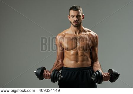 Adorable Bodybuilder Building Up Muscles With Dumbbells Isolated On Grey Background