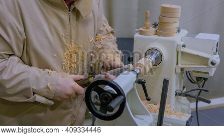 Professional Man Carpenter Using Skew Chisel For Shaping Piece Of Wood On Wood Turning Lathe At Work