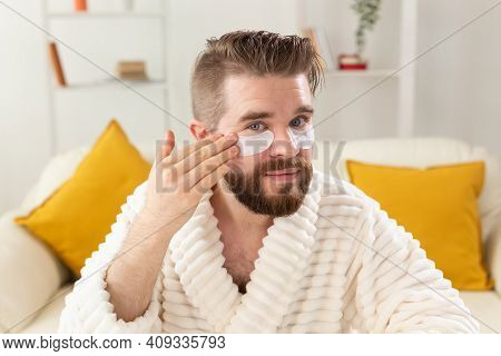 Bearded Man Sitting With Eye Patches On His Face. Wrinkles And Face Home Care For Men.