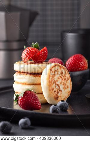 Close Up Of Cheese Pancakes With Fresh Berries On Dark Ceramic Plate. Syrniki. Vertical Photo - Imag