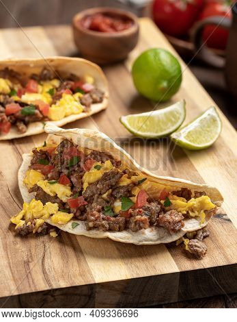 Breakfast Tacos With Scrambled Egg, Sausage And Tomato On A Wooden Cutting Board