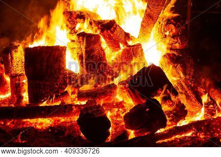 Burning Wooden Logs With Dark Background. Red Flame