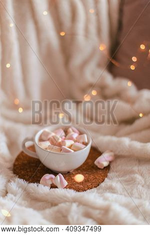 Ceramic Cup Of Hot Chocolate Or Cocoa With Marshmallow On A Cork Stand On A White Bedspread. Decorat