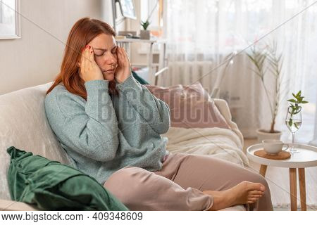 Upset Young Girl Is Suffering From A Headache. Woman In Casual Clothes Sits On The Sofa In Interior.