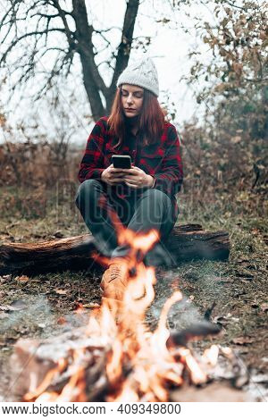 A Young Traveler Girl In A Plaid Shirt And Hat Uses A Smartphone Sitting By The Fire Near The Camp.