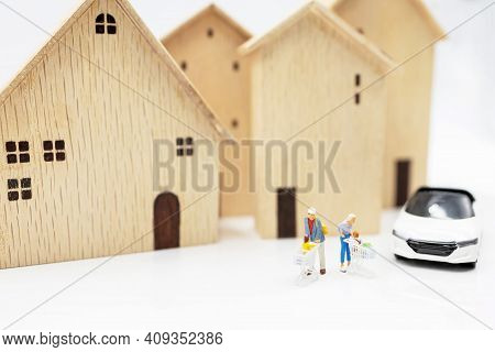 Miniature People: Parent And Children With Shopping Cart Standing On Coins Stack With House And Car.