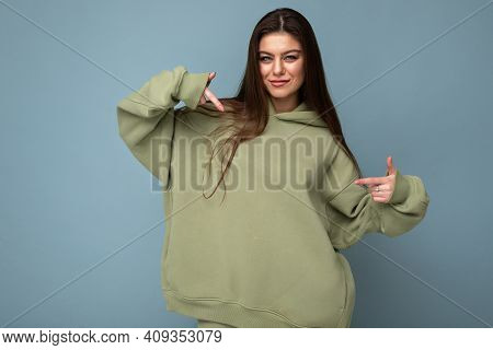 Attractive Young Woman In A Khaki Hoodie. Mock-up. Copy Space.
