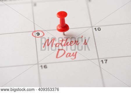 Happy Mother's Day Concept. Cropped Close Up View Photo Of Red Pushpin Attached To Calendar With Ins