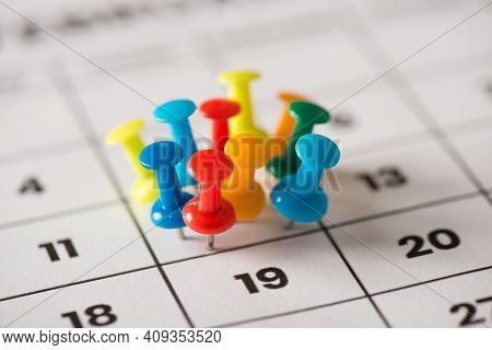 Busy Day Concept. Cropped Close Up View Photo Image Of Lot Of Thumbtacks Attached To The Calendar