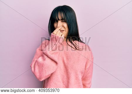 Young brunette woman with bangs wearing casual winter sweater smelling something stinky and disgusting, intolerable smell, holding breath with fingers on nose. bad smell