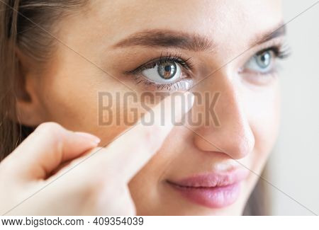 Ophthalmology And Eyecare. Closeup Portrait Of Young Woman Applying Eye Lens. Smiling Female Using A