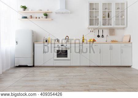 Interior Of Stylish Kitchen With Light Walls, White Furniture With Utensils And Fruits, Shelves With